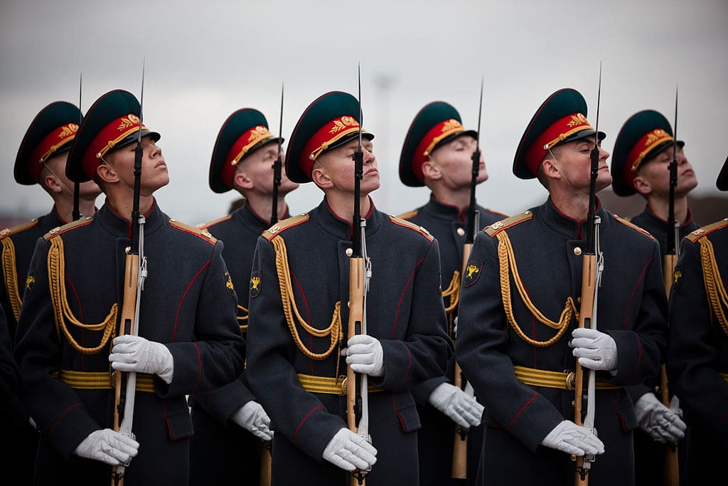 Russian male soldiers standing together with rifles held vertically.