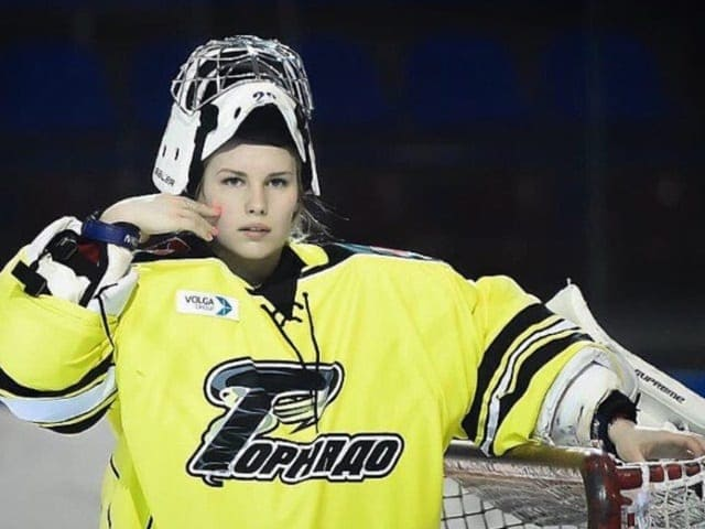Photo of Elizaveta Kondakova holding on to the top of the net next to the goal she is guarding.