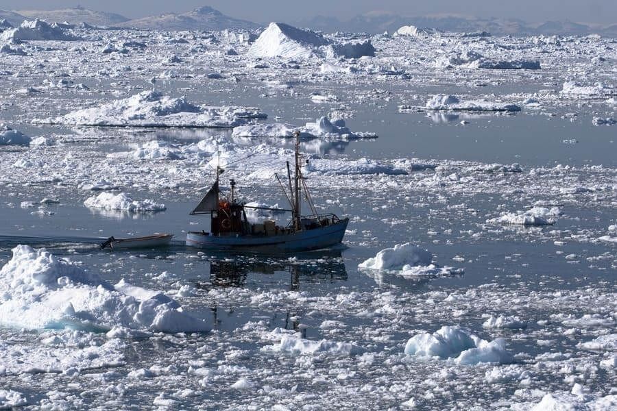 Photograph of a fishing boat going through icy waters.