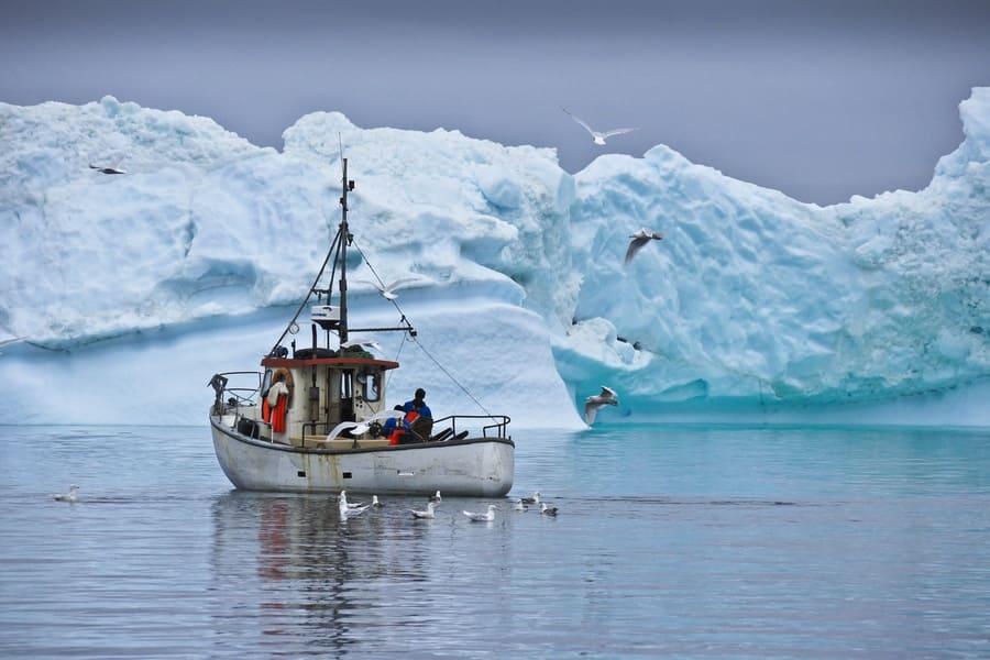 Fishermen are photographed navigating around blue icebergs.