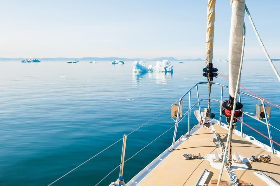 A boat sailing among icebergs in Greenland.