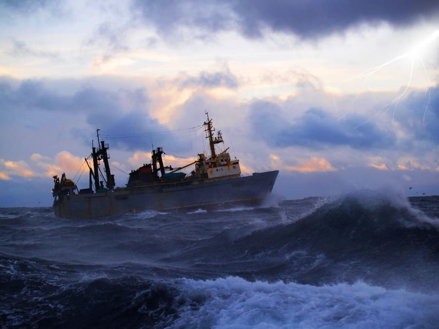 The fishing boat struggles for a life in a storm high water.