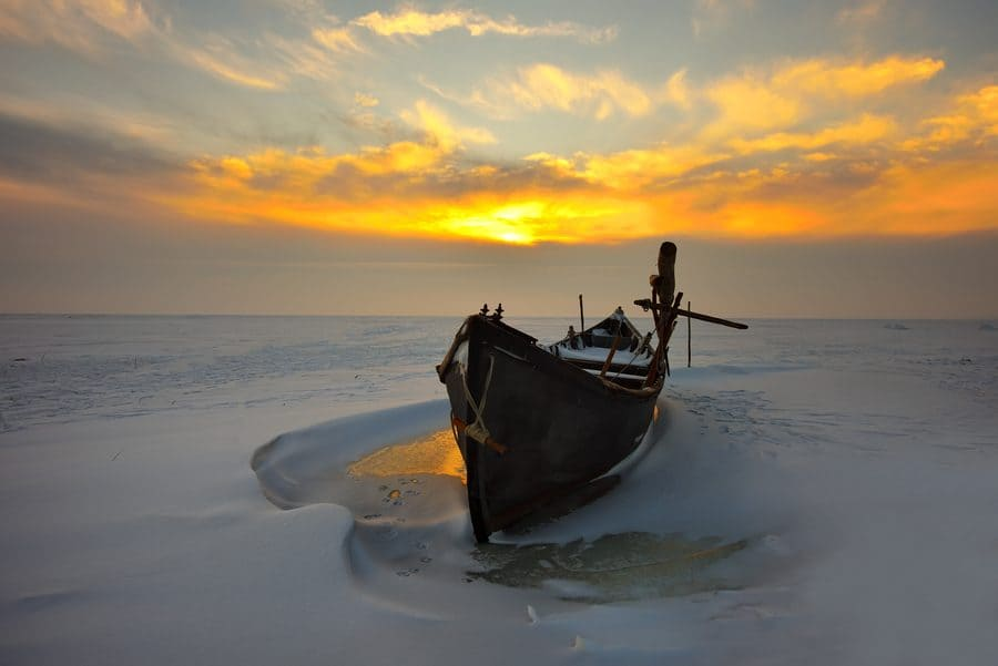 A boat going through icy waters at dusk.