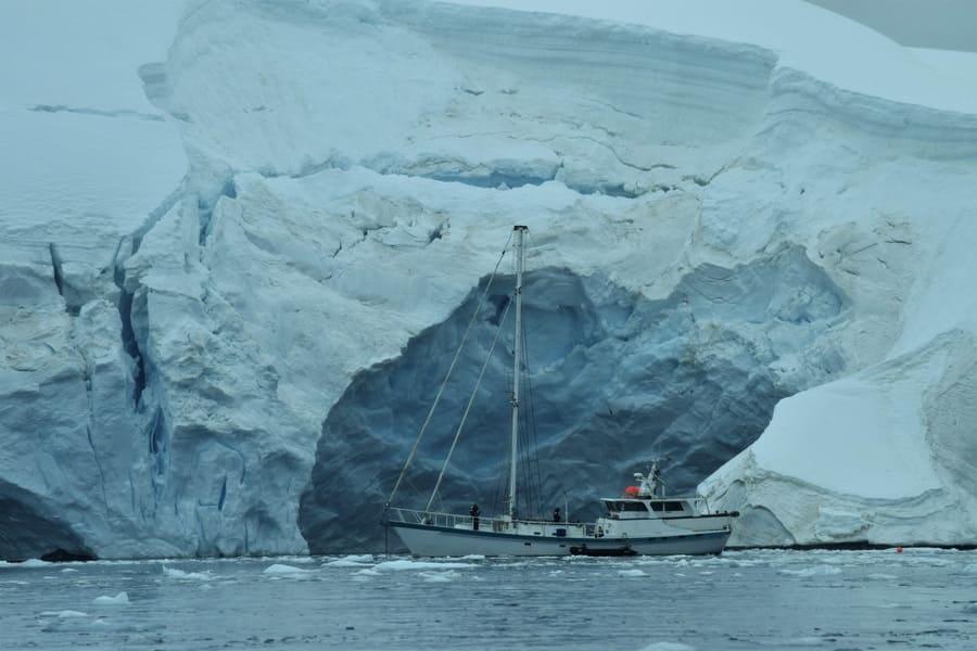 A boat creeping closer to an iceberg at dusk.