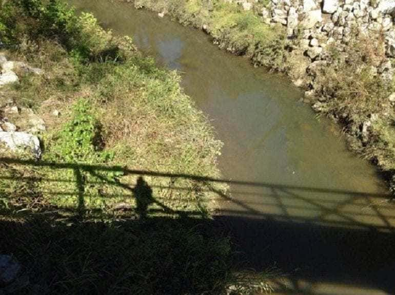 Photograph of a creek and the shadow of someone standing on a bridge taking a photograph.