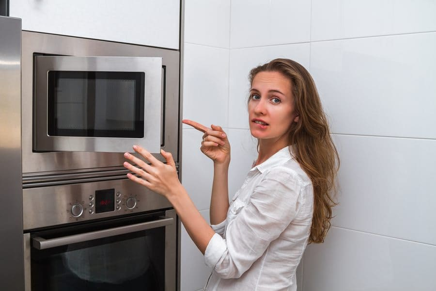 A woman looks like she is not sure what to put into the microwave.