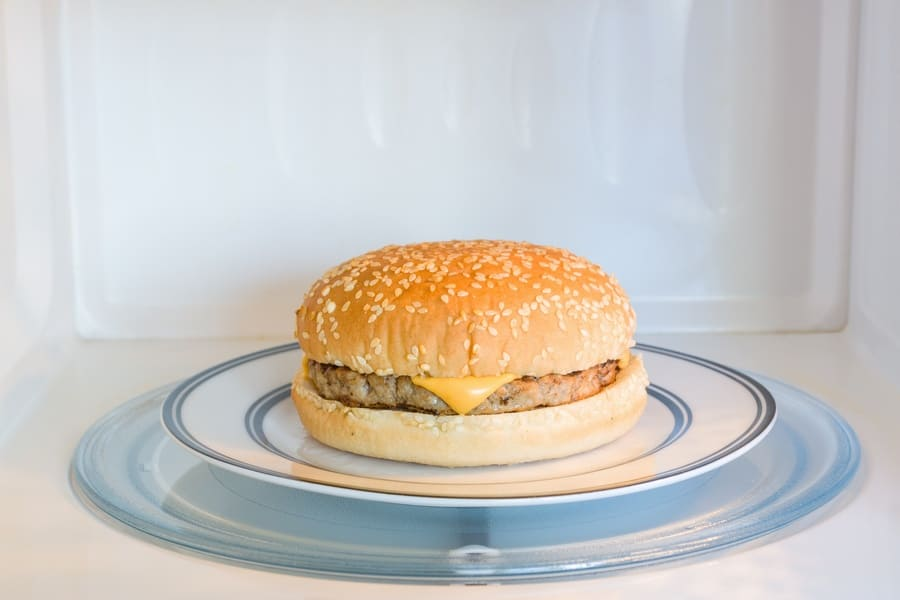 Photograph of a cheeseburger on a plate with designs made of metal components.