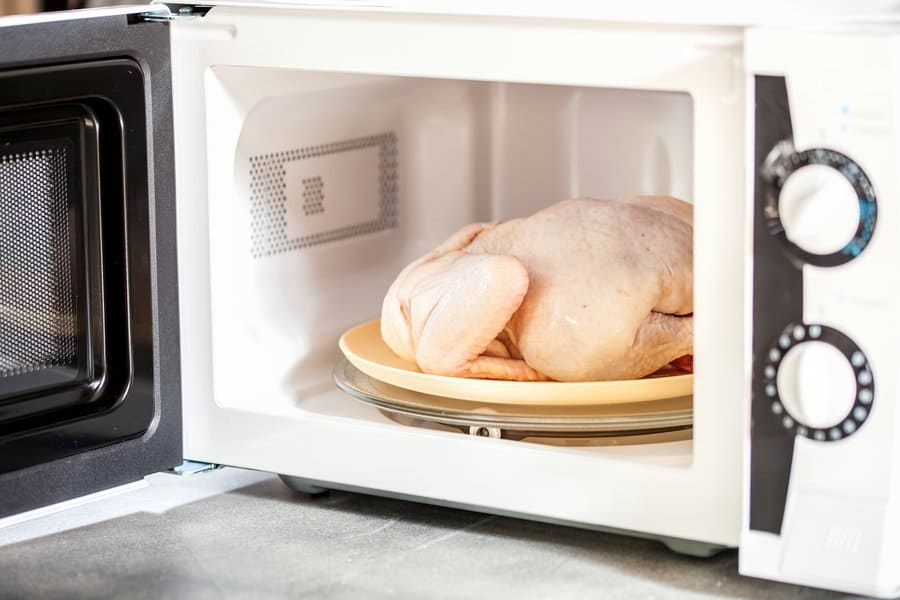Photograph of a raw chicken inside of a microwave.