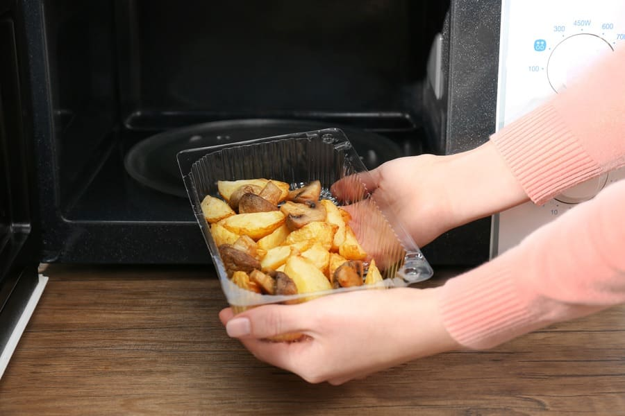 A container with cooked mushrooms and potatoes being placed in the microwave.