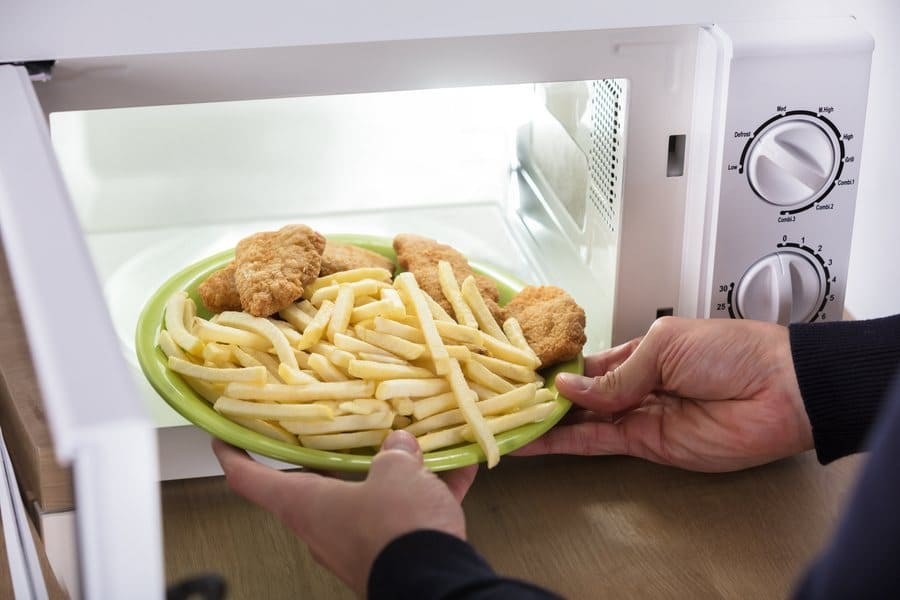 A person putting french fries and fried chicken in the microwave.