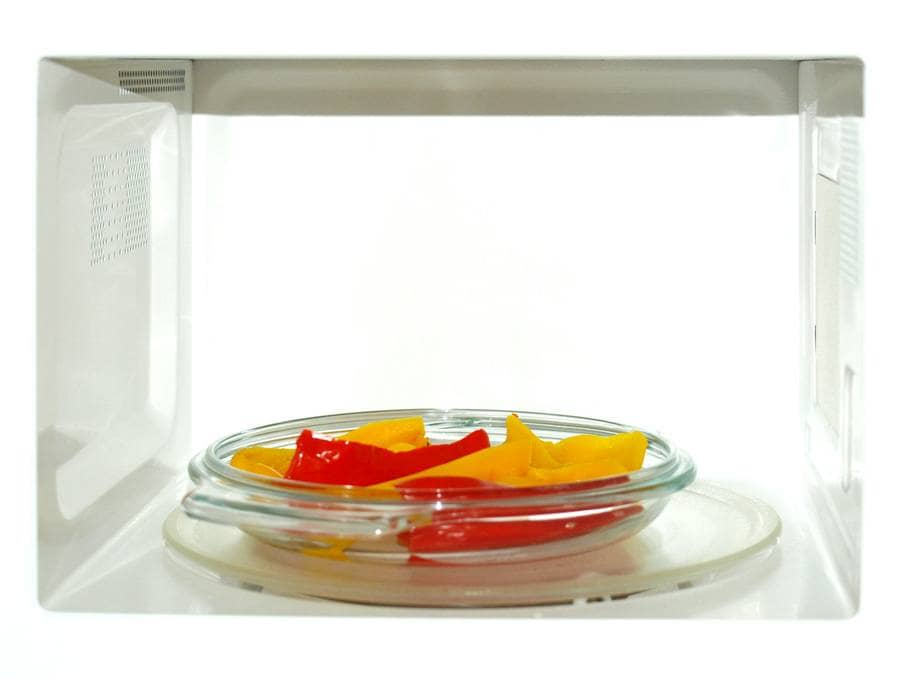 Photograph of peppers sitting on a plate in the microwave.
