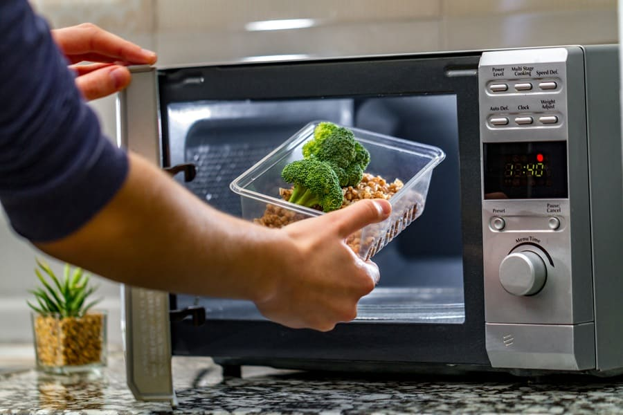 Photograph of a one-time-use plastic container being used to heat up food in the microwave.