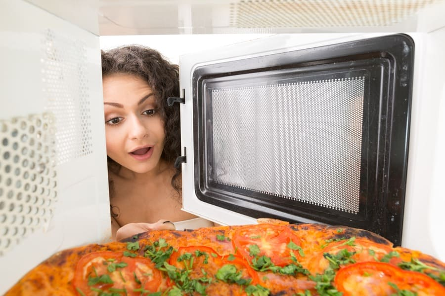 A woman placing a pizza with leafy greens on it in the microwave.