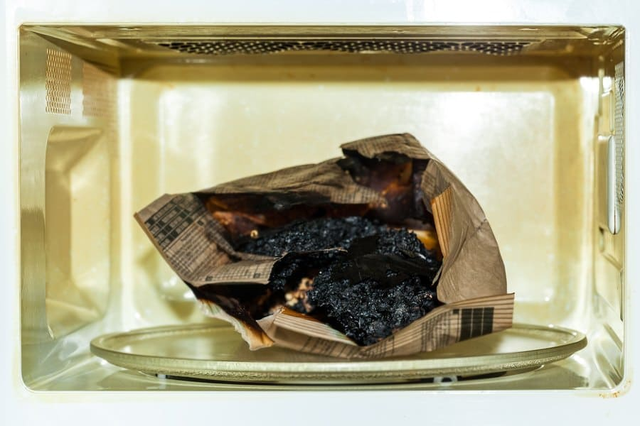 Burnt paper bag with melted and burnt popcorn after a paper bag exploded in the microwave.