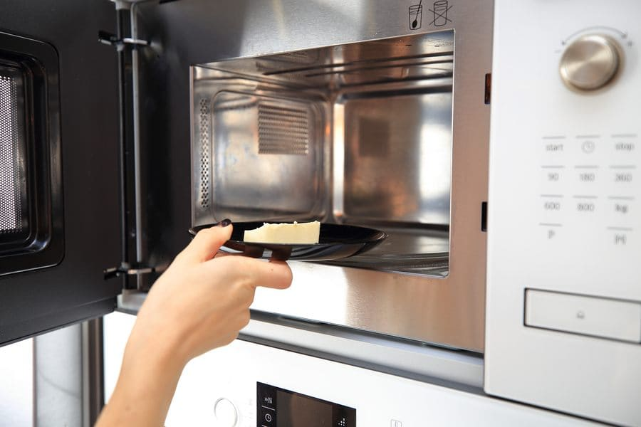 A woman placing butter into the microwave to heat it up.