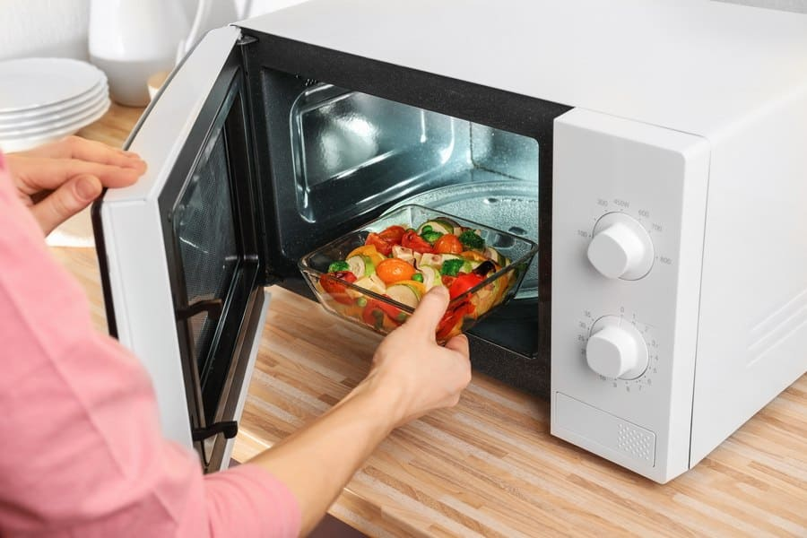 A bowl of vegetables being placed in the microwave.