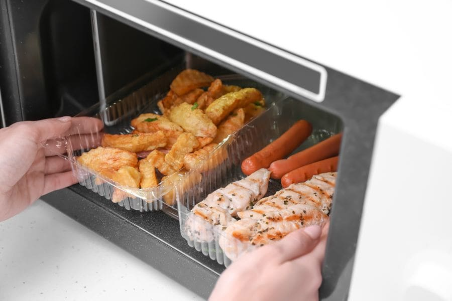 A woman putting a container with fried potatoes, chicken meat and sausages into the microwave.