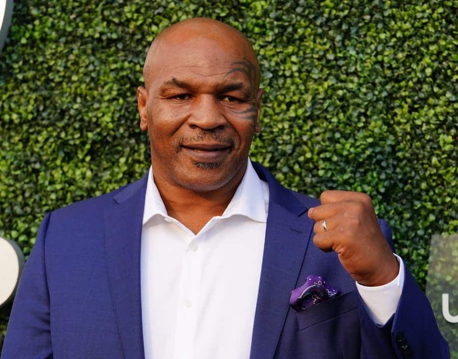 Mike Tyson making a fist standing in front of some bushes.