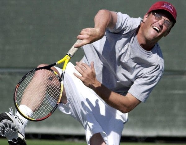 A photo of Matthew Perry making a face while hitting a tennis ball.