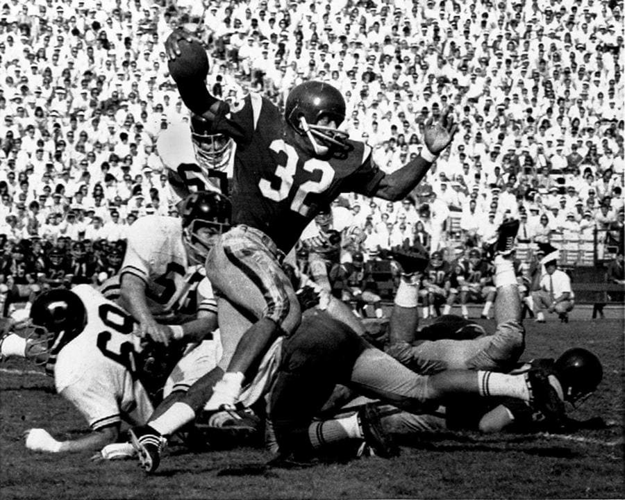 Photograph of OJ Simpson (32) runs against rivals from Cal Berkely during an NCAA game in LA.
