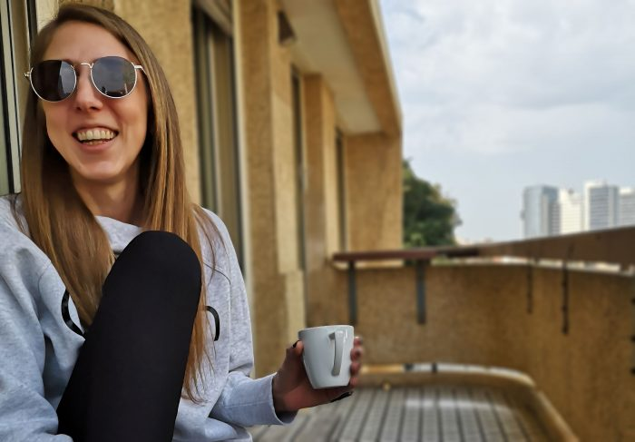Me laughing mid-conversation on the porch holding a cup of coffee.