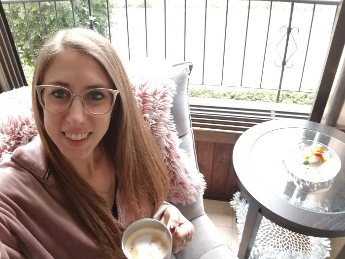 Me sitting on a grey chair in front of a large open window, holding a cup of coffee.