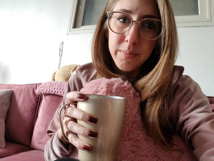 Me sitting on a pink sofa drinking coffee.