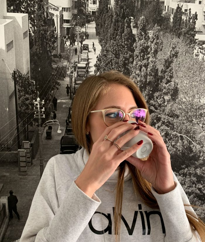 Me drinking a cup of coffee in front of a black and white photograph of a street view.