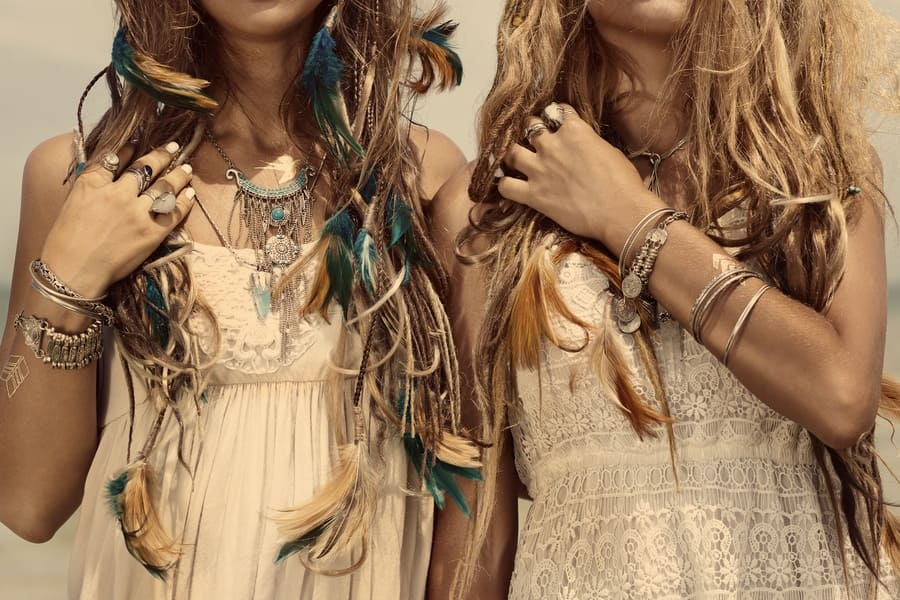Photo of two girls with boho style accessories, feathers, and lace outfits.