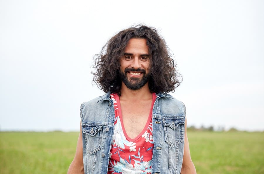 A man with a denim vest and floral shirt standing in a field.