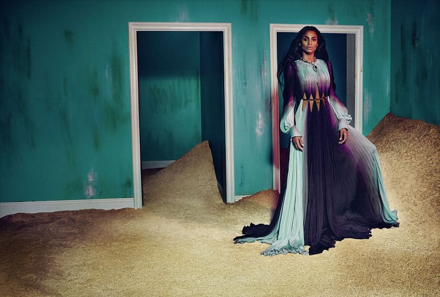 Ciara is wearing a flowing purple and green dress in front of a green wall with sand everywhere.