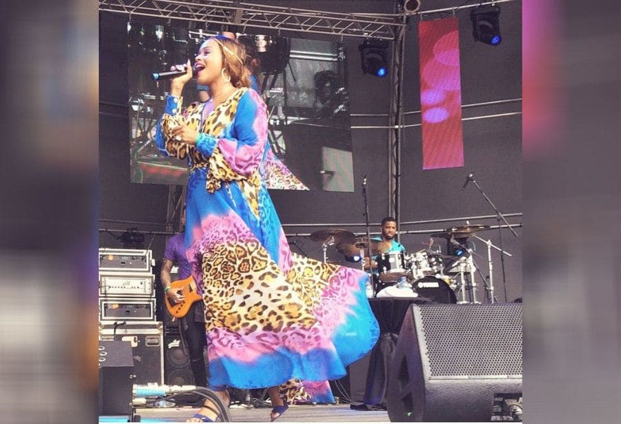 Chrisette Michele in a blue and purple dress with leopard print performing.