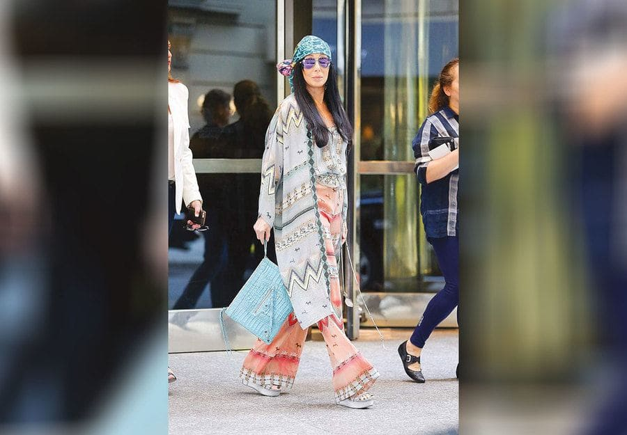 Cher was walking through the street the day after the Met Gala with loose and colorful multi-patterned clothing.
