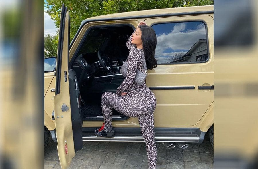 Kylie Jenner is posing in a tight leopard print bodysuit next to her car.
