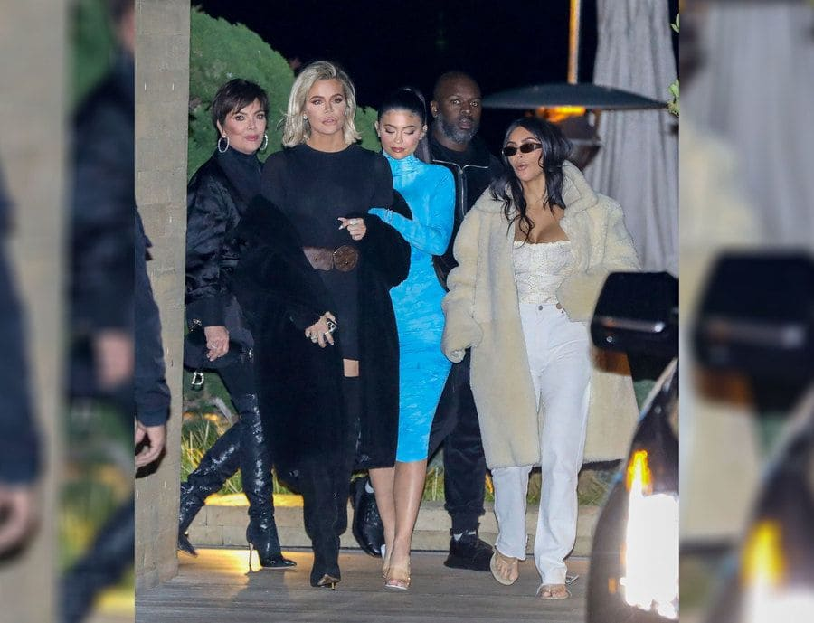 Khloe Kardashian with a short tight black dress and a faux fur coat with tall black boots leaving dinner with her family.