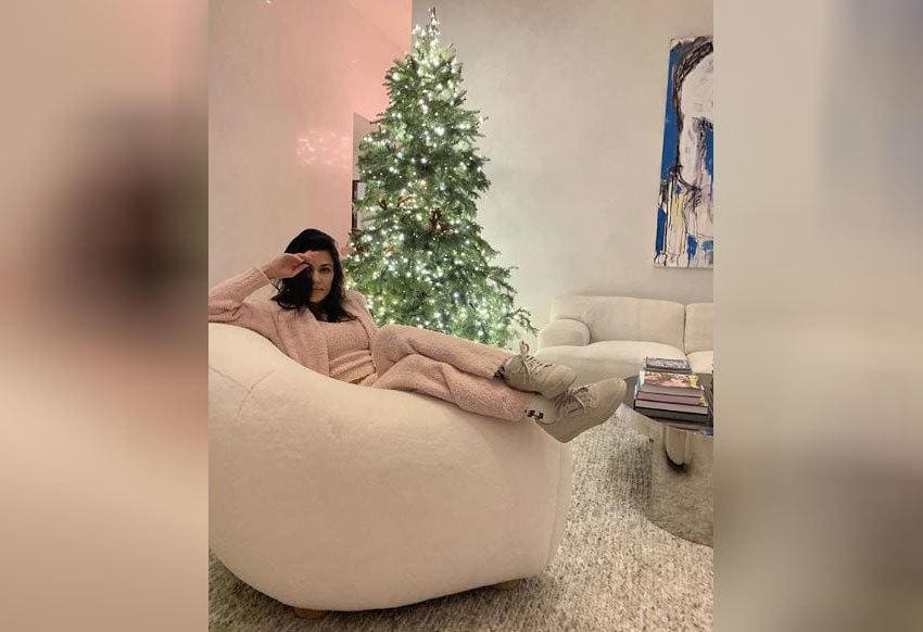 Kourtney Kardashian is sitting on the couch in sneakers and a fluffy light pink outfit.