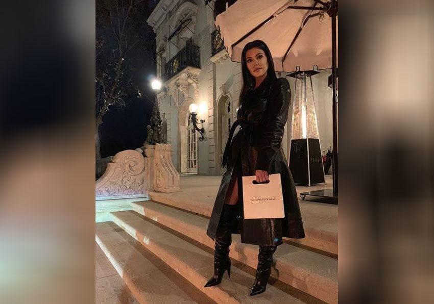 Kourtney Kardashian dressed in all black holding a Victoria Beckham bag.