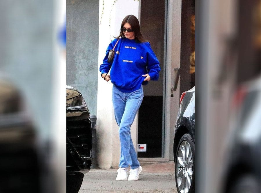 Kendall Jenner is wearing a Kanye West sweater with blue jeans.