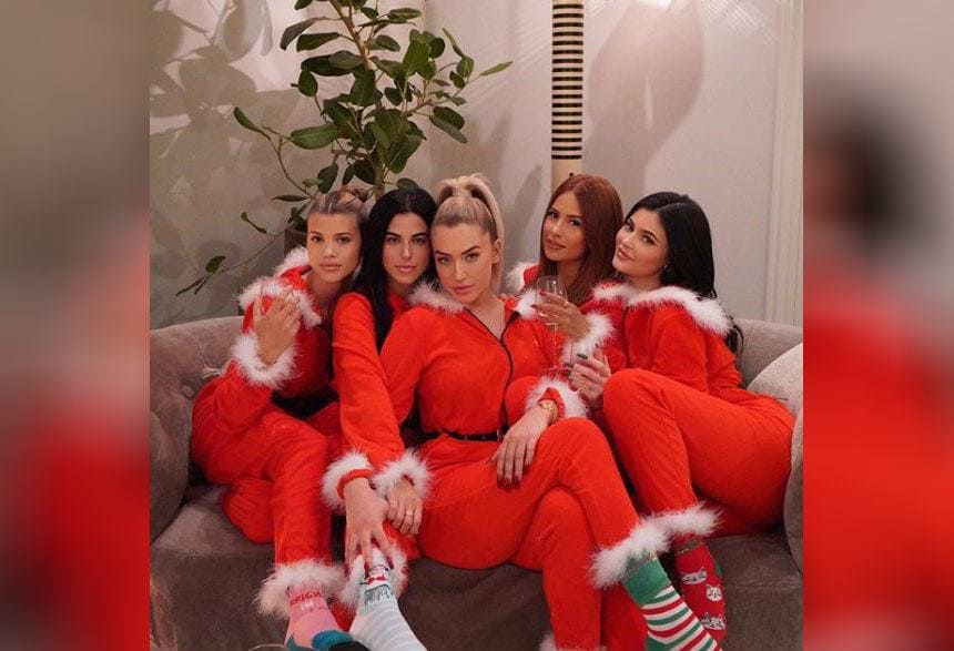 Kylie Jenner with her friends dressed in red onesies with white fur around them.