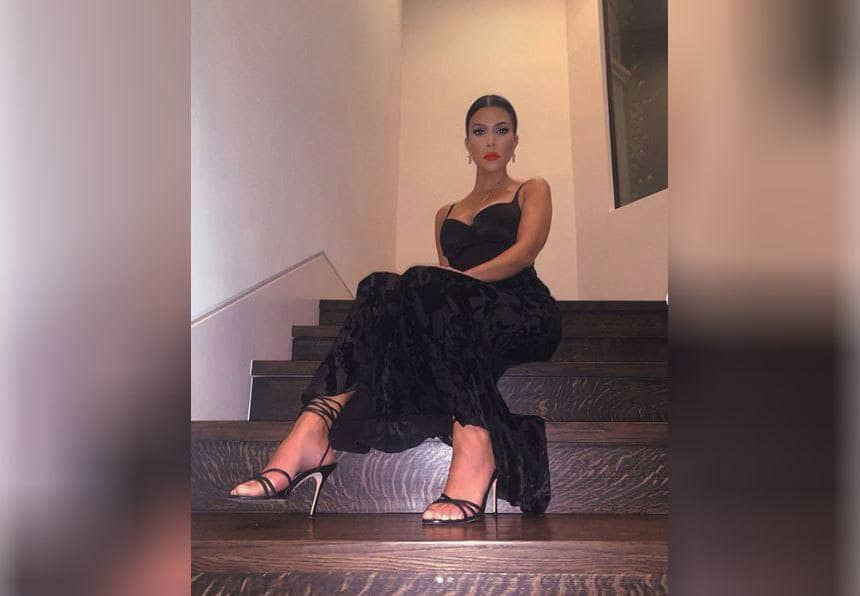 Kourtney Kardashian is posing on her dark wooden steps with a long black dress on.
