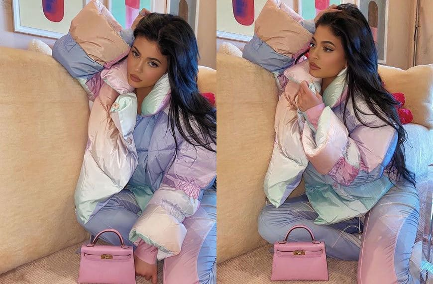 Kylie Jenner in a puffy winter coat with multiple pastel colors and matching pants with a small pink handbag.