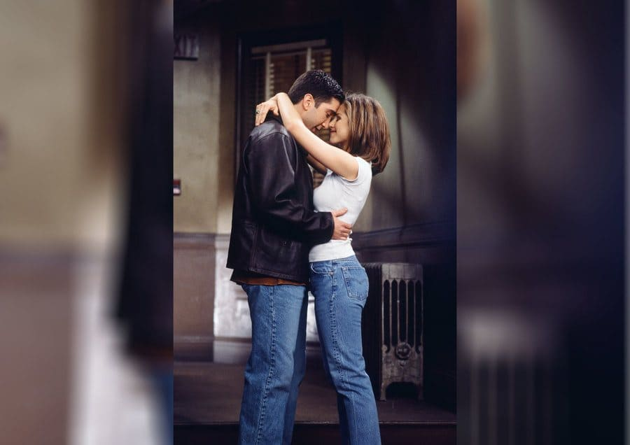 Ross and Rachel about to kiss while Rachel is wearing a short white t-shirt and blue jeans.