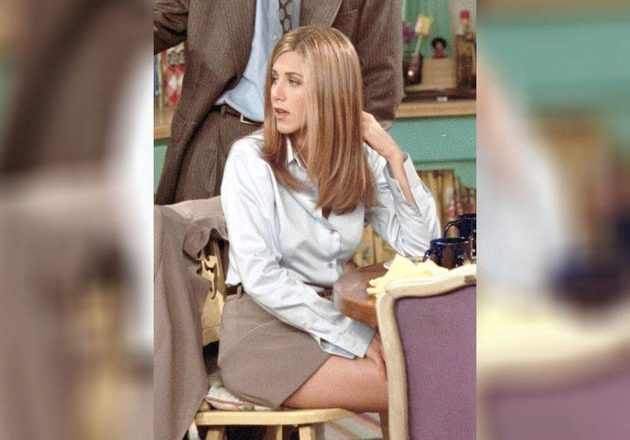 Rachel Green in a button-down shirt and a professional shorter skirt.
