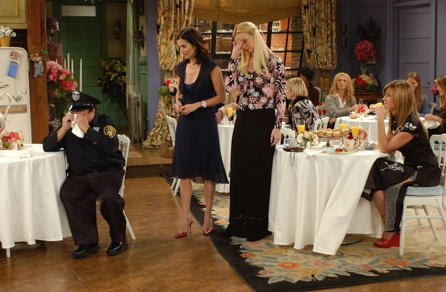 Jennifer Aniston wearing a black short-sleeved floral dress in a scene with Danny DeVito.