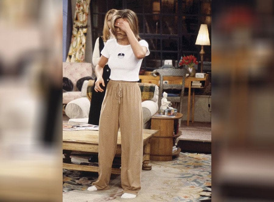 Rachel Green standing in long tan pajama pants and a white t-shirt with a crown on it.