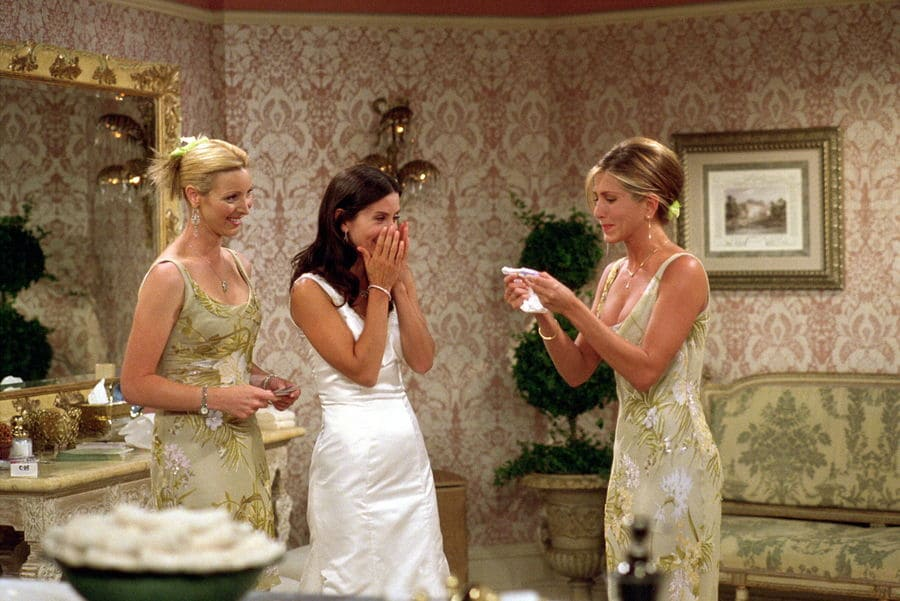 Rachel and Phoebe in matching bridesmaids' dresses with Monica standing in the middle in her wedding dress.