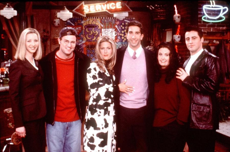 A behind the scenes photo of the whole cast with Rachel standing in the middle in the long cow patterned jacket.