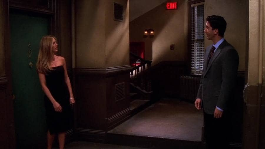 Rachel and Ross in the hallway talking, and Rachel is wearing a strapless black dress with a split.