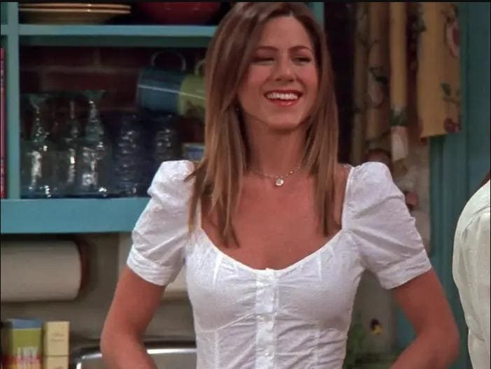 Rachel Green with a white short-sleeved shirt on.