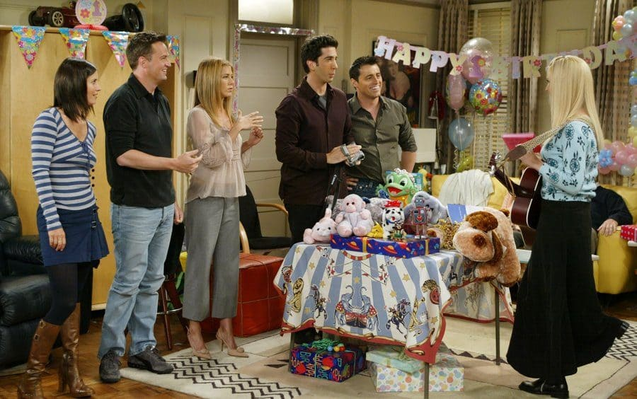 Everyone standing around at Rachel and Ross's children's birthday party while Phoebe plays the guitar.